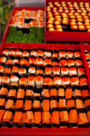 Raw fish sushi is displayed at an outdoor street market stall in Bangkok Imagens