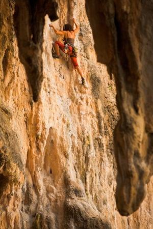 nang: Railay Beach, Thailand - January 31, 2011: A female climber, framed by hanging stalactites, reaches for a hold in Railay beach in Krabi, a hub of rock climbing activities in Thailand January 31, 2011 at Phra Nang Railay Beach, Thailand. Editorial
