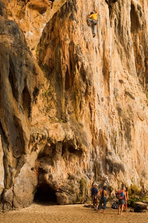 Railay Beach, Thailand - January 31, 2011: A male climber scales the face of a limestone cliff in Railay beach, a hub of rock climbing activities in Thailand January 31, 2011 at Phra Nang Railay Beach, Thailand. Éditoriale