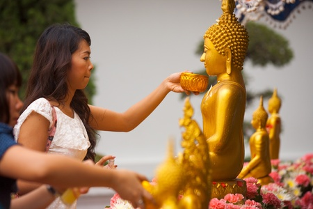 Bangkok, Thailand - April 9, 2011: A Buddhist Thai woman cleans and perfumes a Buddha statue to gain merit, an annual ritual for the holiday of Songkran or Thai New Year April 9, 2011 at Bangkok, Thailand