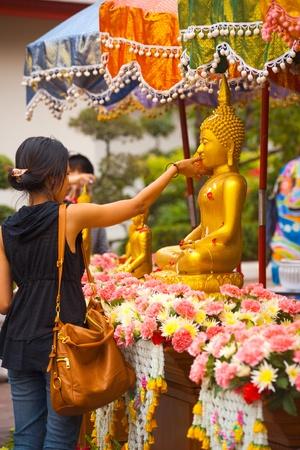 방콕, 태국 - 년 4 월 9 일 : 부처님 동상은 젊은 태국 여자, 방콕, 태국 송크란 또는 태국 설날 2011년 4월 9일의 휴가를위한 연례 의식에 의해 물 청소