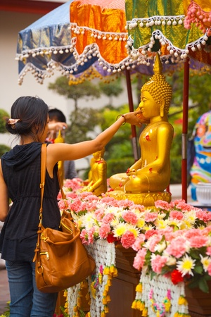 Bangkok, Thailand - April 9, 2011: A Buddha statue is cleaned with water by a young Thai woman, an annual ritual for the holiday of Songkran or Thai New Year April 9, 2011 at Bangkok, Thailand 新聞圖片
