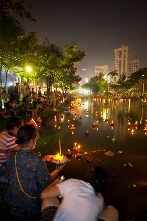 BANGKOK - NOVEMBER 21, 2010: Thai people launch candle lighted krathongs at downtown Lumpini park during the annual Thai holiday festival of Loi Krathong on November 21, 2010 in Bangkok