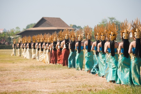 surin: SURIN, ISAN, THAILAND - NOVEMBER 20, 2010: A row of traditionally dressed Thai dancers walk on to the field at the annual Surin Elephant Roundup on November 20, 2010 in Surin, Thailand