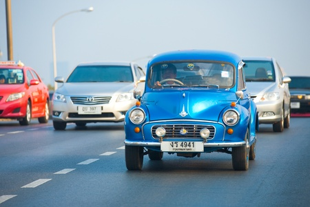 BANGKOK, THAILAND - NOVEMBER 10, 2010: A Thai man drives a vintage, restored, mint-condition, blue Morris Minor, a classic collector's car, on the road on November 10, 2010 in Bangkok, Thailand