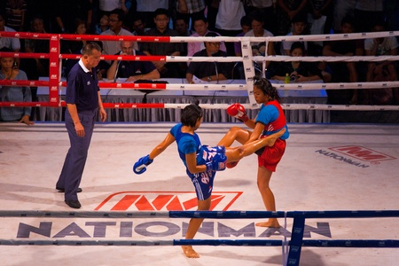 BANGKOK, THAILAND - NOVEMBER 17, 2010: A kick from a female muay thai kickboxer is blocked at Fight Night at MBK on November 17, 2010 in Bangkok, Thailand