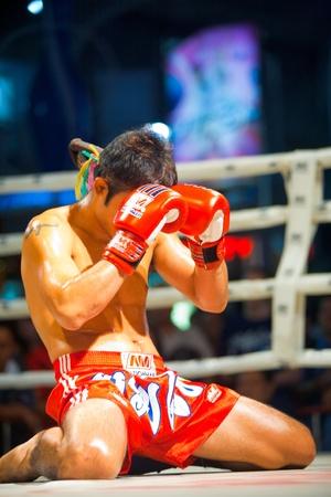 방콕, 태국 - 2010년 12월 8일 : 무에타이 킥 복서가 미리 싸움을 의식하는 동안 자신의 장갑으로 그의 얼굴을 무릎을 꿇고 커버 방콕, 태국에서 2010 년 12  에디토리얼