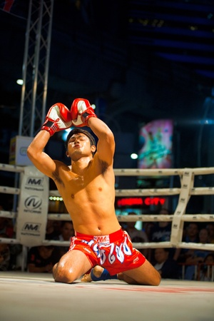BANGKOK, THAILAND - DECEMBER 8, 2010: A kneeling muay thai kickboxer raises his arms and chants during a pre- kickboxing ritual called the wai khru on December 8, 2010 in Bangkok, Thailand