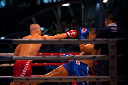BANGKOK, THAILAND - NOVEMBER 17, 2010: A lunging muay thai kickboxer misses a punch at his opponent at Fight Night at MBK on November 17, 2010 in Bangkok, Thailand