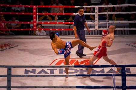 BANGKOK, THAILAND - NOVEMBER 17, 2010: A caucasian muay thai kickboxer dodges a kick from his Thai opponent at Fight Night at MBK on November 17, 2010 in Bangkok, Thailand Stock Photo - 13574474