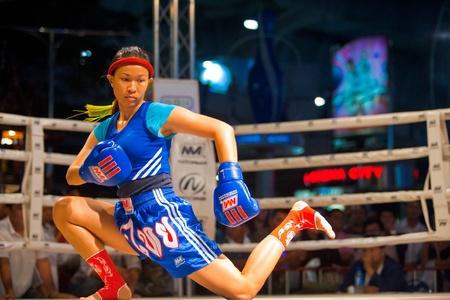 BANGKOK, THAILAND - DECEMBER 8, 2010: A female muay thai kickboxer performs a knee down kicking routine during a pre- kickboxing ritual called the wai khru on December 8, 2010 in Bangkok, Thailand