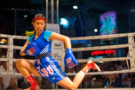 BANGKOK, THAILAND - DECEMBER 8, 2010: A female muay thai kickboxer performs a knee down kicking routine during a pre- kickboxing ritual called the wai khru on December 8, 2010 in Bangkok, Thailand
