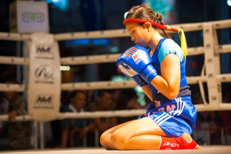 BANGKOK, THAILAND - DECEMBER 8, 2010: An unidentified female muay thai fighter reflects in a kickboxing ritual called the wai khru meant to honor her teachers on December 8, 2010 in Bangkok, Thailand Editöryel