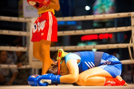 BANGKOK, THAILAND - DECEMBER 8, 2010: An unidentified female muay thai fighter bows her head on the ring to perform a kickboxing ritual called the wai khru on December 8, 2010 in Bangkok, Thailand