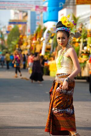 SURIN, ISAN, THAILAND - NOVEMBER 19, 2010: A traditionally dressed beauty queen walks in the parade through downtown at the annual Surin Elephant Roundup on November 19, 2010 in Surin, Thailand