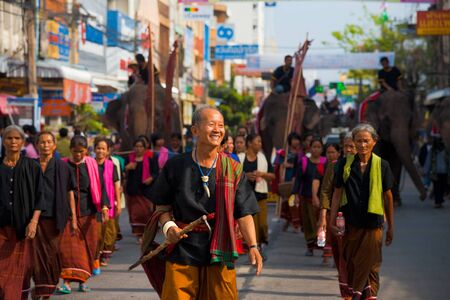 SURIN, ISAN, THAILAND - NOVEMBER 19, 2010: A Surin village elder leads a group of traditional dress villagers in a parade at the annual Surin Elephant Roundup on November 19, 2010 in Surin, Thailand
