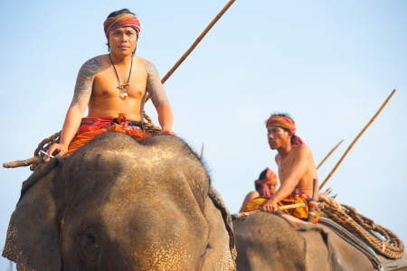 SURIN, ISAN, THAILAND - NOVEMBER 19, 2010: Traditionally dressed trainers ride high on the backs of their elephants at the annual Surin Elephant Roundup parade on November 19, 2010 in Surin, Thailand