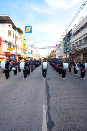SURIN, ISAN, THAILAND - NOVEMBER 19, 2010: A group of high schoolers play music  as a marching band in a parade at the annual Surin Elephant Roundup on November 19, 2010 in Surin, Thailand. Vertical