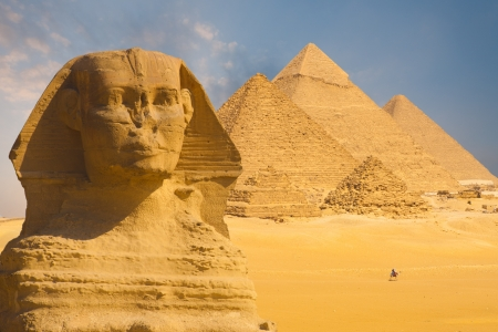 A closeup of the face of the Great Sphinx with a set of pyramids in the background on a beautiful clear blue sky day in Giza, Cairo, Egypt photo