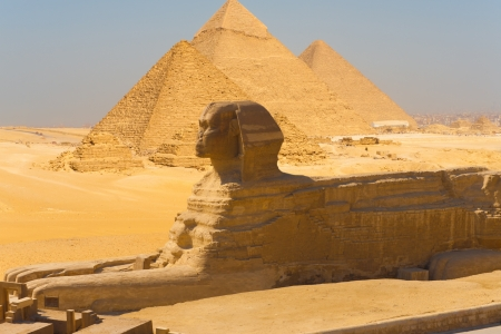 Sphinx: A side view of the great Sphinx with all of the pyramids of Giza in the background in Cairo, Egypt