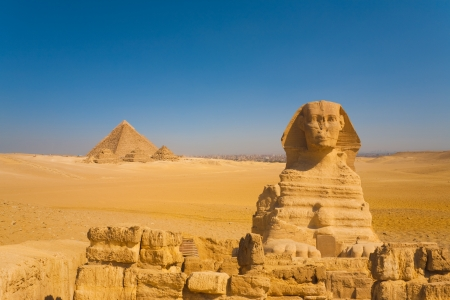 The sphinx stands guard to a distant set of Giza pyramids in a vast desert with the city of Cairo in the background, Egypt