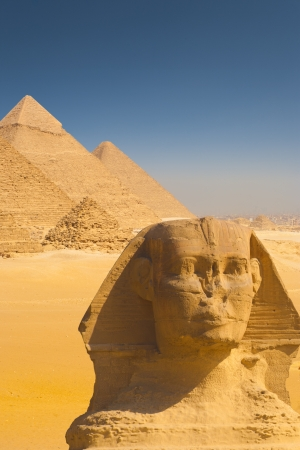 A beautiful composite of the Giza pyramids behind a closeup of the head of the great Sphinx in Cairo, Egypt photo
