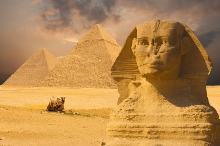 The Great Sphinxs face with a set of pyramids in the background and a beautiful purple sunset sky day in Giza, Cairo, Egypt Stock Photo