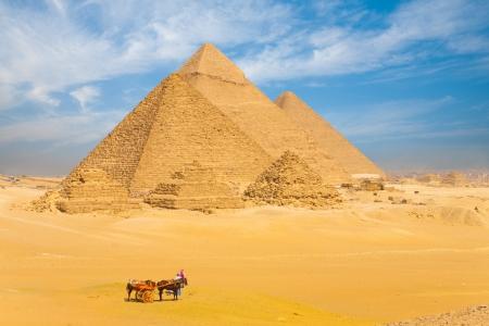 piramide humana: Las pirámides de Giza se alinearon en una fila frente a un hermoso cielo azul en El Cairo, Egipto