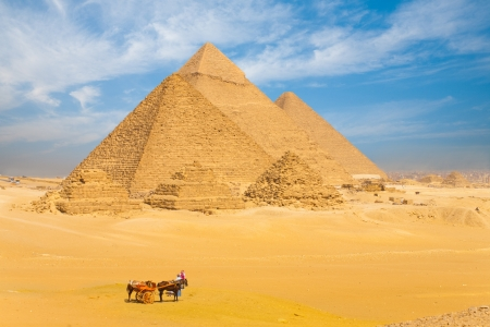 The Giza pyramids lined up in a row against a beautiful blue sky in Cairo, Egypt