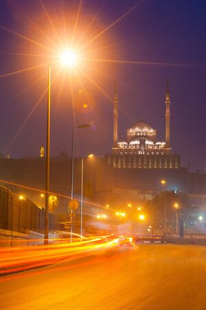 The Citadel in Cairo is illuminated by lights at night with trailing lights of cars on the street below in Egypt photo
