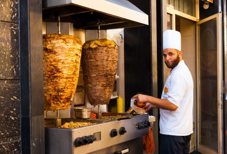 cairo: CAIRO - OCTOBER 13, 2010: A male Egyptian cook prepares a Middle East staple food on a sidewalk grill on October 13, 2010 in Cairo. Kebab is a cheap, fast food sandwich widely consumed in Egypt Editorial