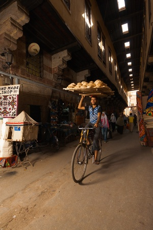 cairo: CAIRO - OCTOBER 19, 2010: A bicycle delivery man precariously rides with a tray of bread on his head at the Souq All Khiamiyya, Tentmakers Bazaar, a tourist attraction on October 19, 2010 in Cairo