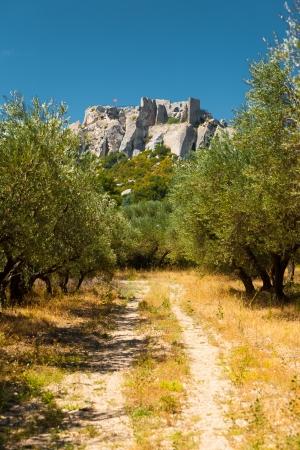 provencal: A picturesque rural dirt road leads to the historic Chateau Des Baux, a castle ruins atop a scenic rocky outcrop in Les Baux de Provence in France