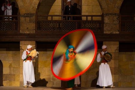 whirling: CAIRO, EGYPT - JULY 3, 2010: An Egyptian Sufi dancer twirls in a motion blurred whirling dervish at an open air courtyard performance, a famous tourist attraction in Cairo, Egypt on July 3, 2010
