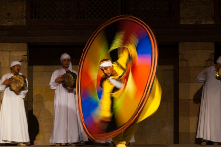 CAIRO, EGYPT - JULY 3, 2010: An Egyptian Sufi dancer in yellow spins during a whirling dervish at an open air courtyard performance, a famous tourist attraction in Cairo, Egypt on July 3, 2010 新聞圖片