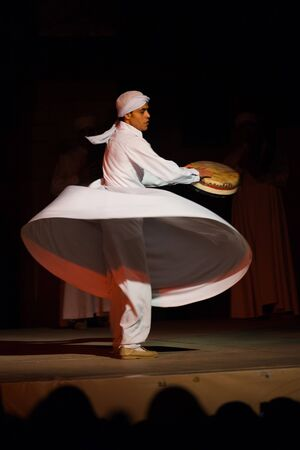 whirling: CAIRO, EGYPT - JULY 3, 2010: A Sufi dancer in white spins and beats a drum during a whirling dervish at an open air courtyard performance, a famous tourist attraction in Cairo, Egypt on July 3, 2010 Editorial