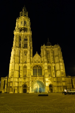 lighted: The facade of the Cathedral of Our Lady and its open square lighted by night lights in Antwerp, Belgium