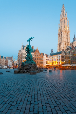 At blue hour, a statue of Brabo stands in the center of the main square of Grote Markt with the Cathedral of Our Lady in the background in Antwerp, Belgium