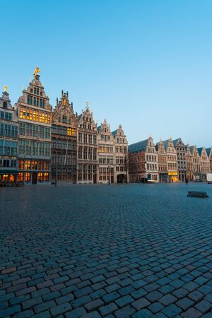 The historic guild houses of Antwerp stand in the large Grote Markt plaza in the evening blue hour in Antwerp, Belgium photo