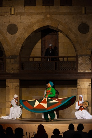 whirling: CAIRO, EGYPT - JULY 3, 2010: A Sufi dancer in green spins during a whirling dervish performance, a famous tourist attraction, at an open air courtyard in Cairo, Egypt on July 3, 2010. Vertical Editorial