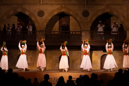 sufi: CAIRO, EGYPT - JULY 3, 2010: A row of Sufi dancers in white play tamborine during a whirling dervish performance, a famous tourist attraction, at an open air courtyard in Cairo, Egypt on July 3, 2010