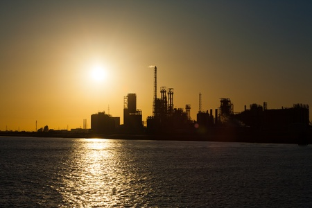 A silhouette of a petrochemical or oil refinery on the ocean against the setting sun in Antwerp, Belgium. Implications of climate change and global warming H
