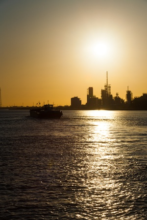 implications: A silhouette of a boat and a petrochemical or oil refinery on the ocean against the setting sun in Antwerp, Belgium. Implications of climate change and global warming V
