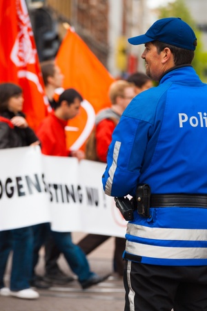 marchers: ANTWERP, BELGIUM - MAY 1, 2010: A friendly Flemish Policeman smiles and watches over marchers at the annual May Day Parade on May 1, 2010 in Antwerp, Belgium Editorial