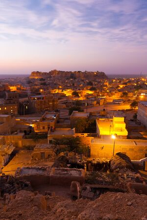 A beautiful morning sunrise around the homes and the distant fort in Jaisalmer, Rajasthan, India.  Vertical photo