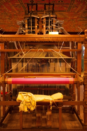 weavers: The weavers chair on the rear of a large wooden handloom in the process of making a pink Indian sari