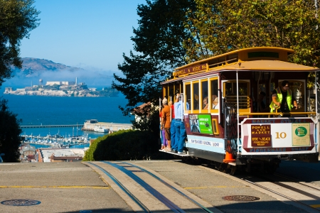 SAN FRANCISCO, USA - SEPTEMBER 21, 2011: Powell Hyde cable car, an iconic tourist attraction, descends a steep hill overlooking Alcatraz prison and SF bay on September 21, 2011 in San Francisco, USA 新聞圖片