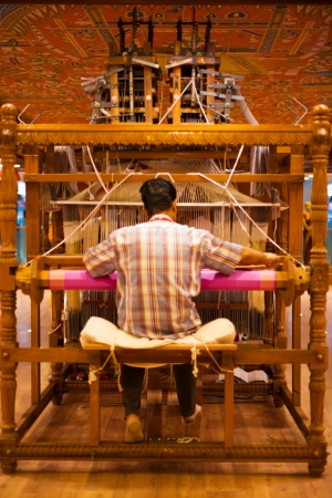 TIRUNELVELI, INDIA - DECEMBER 9, 2009: An unidentified Indian man makes a traditional sari to demonstrate a handloom on December 9, 2009 in Tirunelveli, India