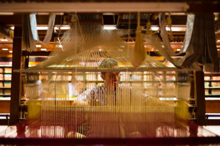 loom: TIRUNELVELI, INDIA - DECEMBER 9, 2009: A unidentified Indian man makes a traditional sari to demonstrate a hand loom on December 9, 2009 in Tirunelveli, India. Textile industry is important for India