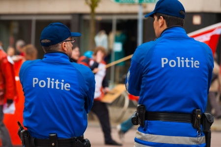 marchers: ANTWERP, BELGIUM - MAY 1, 2010: Two Flemish Policemen watch over marchers and keep the peace at the annual May Day Parade on May 1, 2010 in Antwerp, Belgium Editorial
